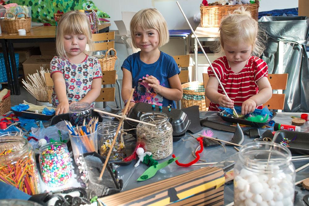 Tre barn pysslar i Ruskpricken. Framför dem ett bort fullt med pysselmaterial.