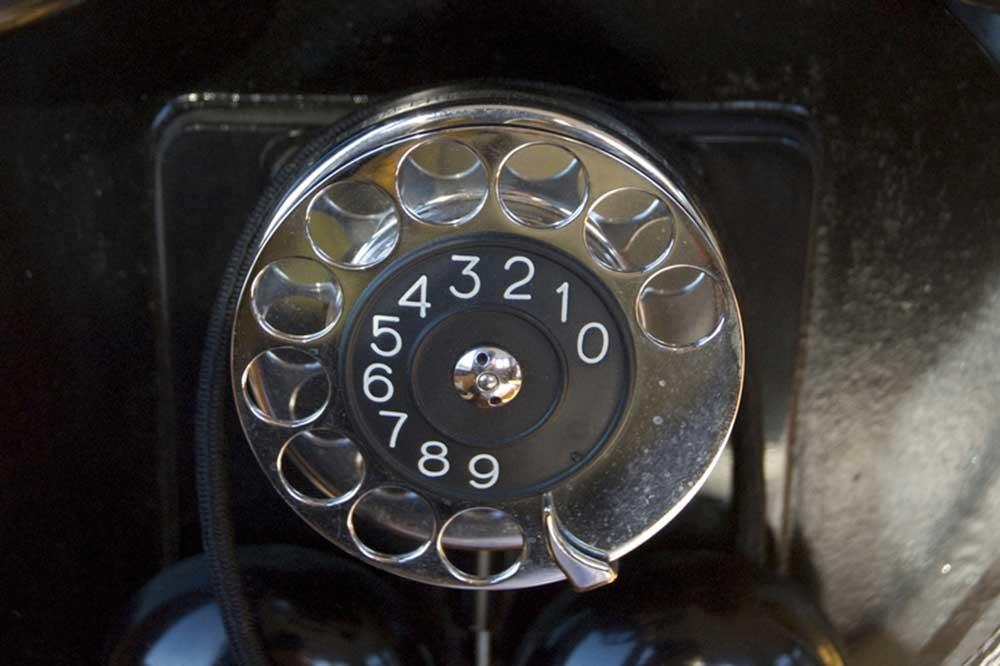 Närbild på nummerskiva på gammal telefon.