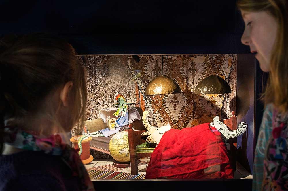 Två barn tittar in i ett tittskåp. I tittskåpet syns figurer i en liten säng och en soffa. På golvet står en jordglob.